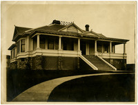 House seen from front yard circular boardwalk, with prominent front steps, large front porch and widow's walk on roof