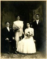 Two unidentified couples in formal dress pose for studio portrait