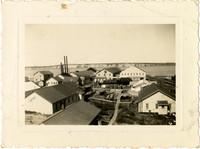 View over rooftops of Pacific American Fisheries Naknek Cannery, Alaska, with boardwalks between buildings, water in distance