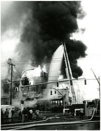 A firetruck's ladder sprays water on large structure fire as smoke billows in air, with multiple fire hoses strung across street in foreground