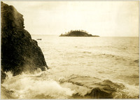 Waves crash over rocky shore with open sea beyond and small boat with three passengers moves to the left