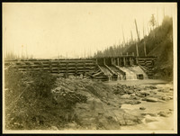 A dam on the Columbia River, made of crisscrossed logs with water flowing out of several gates into rocky stream bed