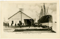Several men stand on dock at Sehome wharf, Bellingham Bay, with large steamship