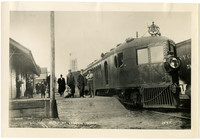 Depot scene with train on right and people standing on platform on left