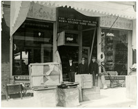 Three men standing at the entrance to The Jenkins-Boys Co. New & Second-Hand Goods
