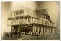 Exterior of hotel with wrap-around porch and balconies, with a numberof people posed on steps and deck