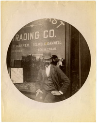 "Man sits in front of ""Gamwell and Warner Real Estate Trading Company"""