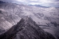 Damaged peak east of mountain, snow-covered ridge in background.