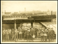 Several dozen workmen stand in front of Loggie's Mill warehouse, with separate photograph attached above