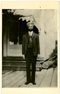 An unidentified man with a beard in a three piece suit, wearing a turban.