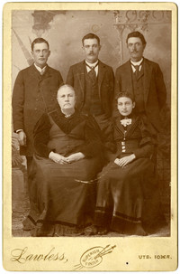 Studio portrait of two seated women, three standing men, of varying ages