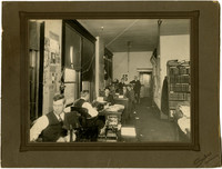 Business or clerical office with several men working at desks with typewritters