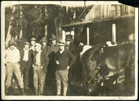 Eight men stand next to horses in front of barn