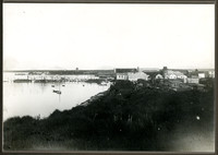 Small seaside village with pier and warehouse, and rolling grassy knolls in foreground