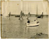 Seven single-masted fishing skiffs on water