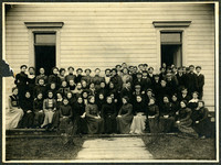 Large group of young men and women pose in several rows outside building, possibly schoolhouse